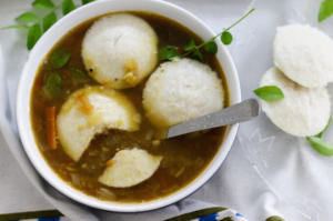 rice idlis dunked in spicy sambar curry